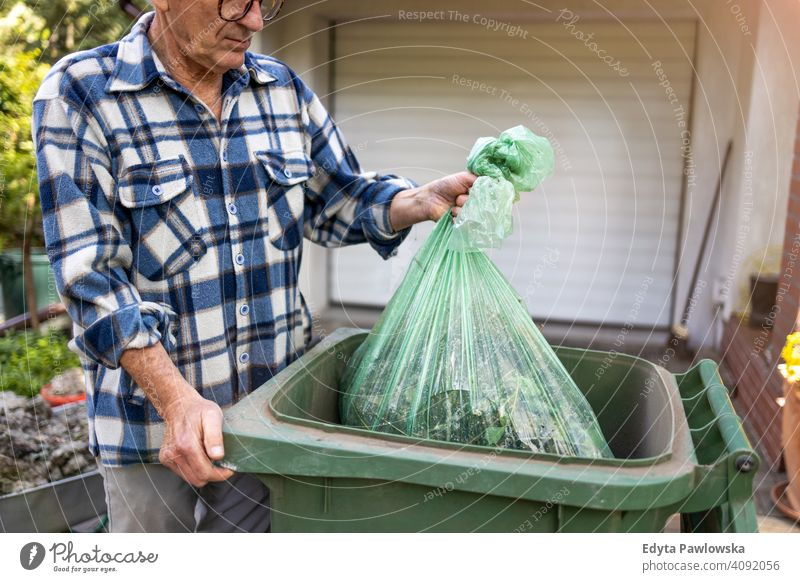 Senior man taking out garbage senior elderly grandfather old pensioner retired retirement aged mature home house male people lifestyle domestic life real people
