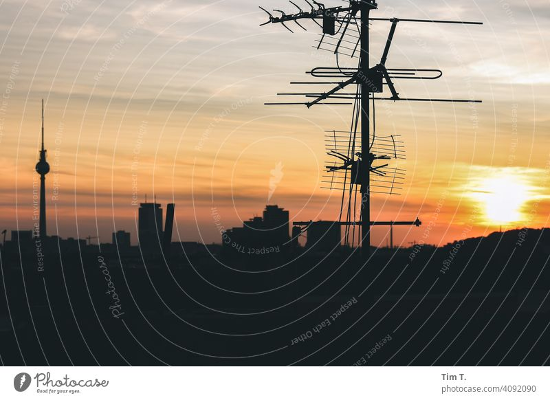 on a roof at sunset in Berlin . In the picture are an antenna and the Berlin TV tower Television tower Sunset Antenna tv tower Sky Berlin TV Tower Landmark