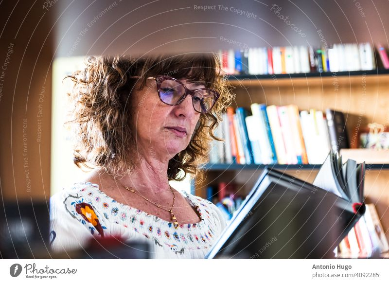 Middle-aged woman reading a book in her library. View through the books. middle aged home indoors literature eyeglasses intelligence intellectual senior