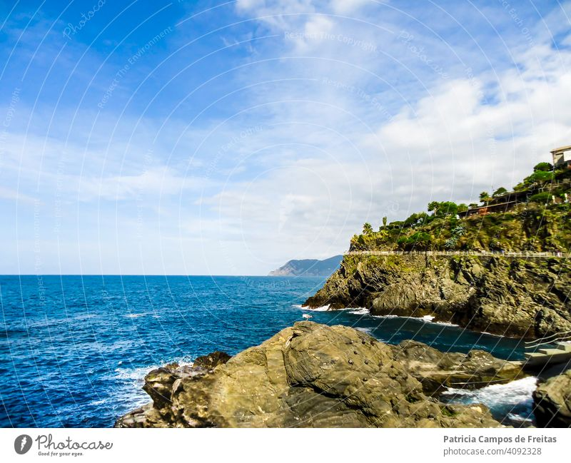 Cliff and rocks by a blue sea, on a sunny day Europa Europe Italia Italy beach blue ocean blue sky cinque terre cliffs costa italiana italy coast landscape