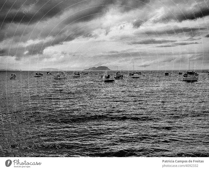 Black and white captures of several small fishing boats at the sea on a clouded day Sea Ocean photography dramatic anchored cloudy sky stormy sea beach