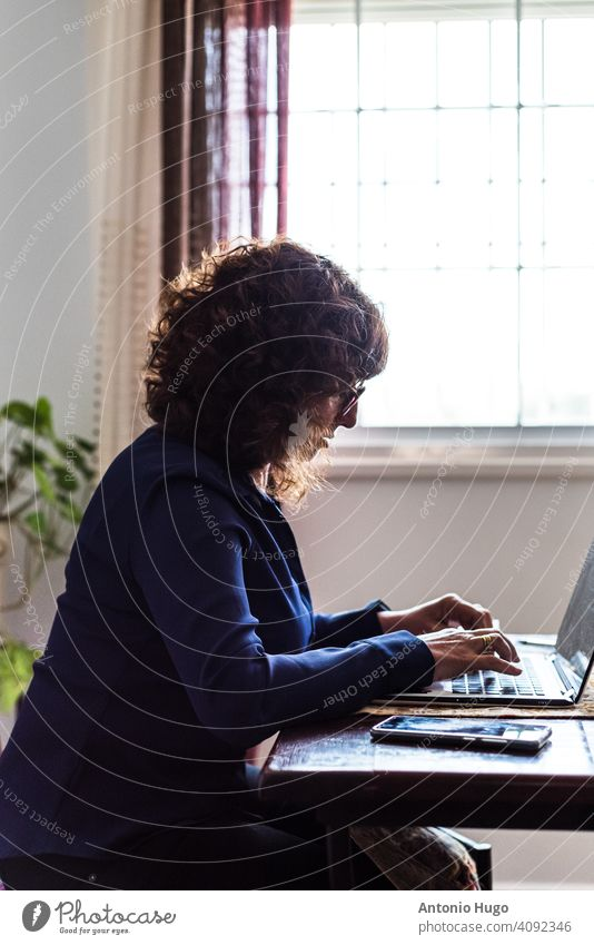 Side view of a middle-aged woman working with laptop computer in her living room. side view mature middle aged home teleworking sitting indoor communication