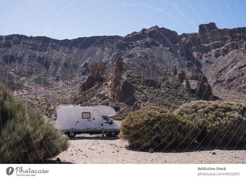 Camper on road against rocky mountains camper wild desert freedom caravan road trip tourism journey spain tenerife nature adventure bush landscape way traveling