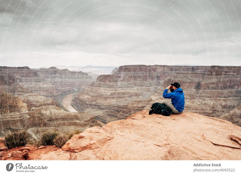 Male relaxing on cliff and admiring picturesque view canyon rest rock admire tranquil backpack jacket usa nature lifestyle hiking active sportswear sit mountain