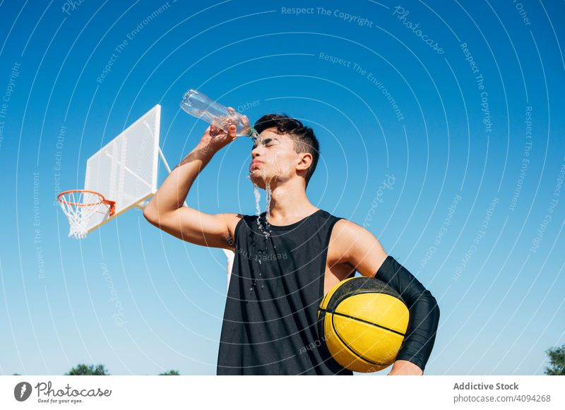 Young man standing with ball and playing on basketball court outdoor. athlete competition sports equipment adult recreation action portrait active activity