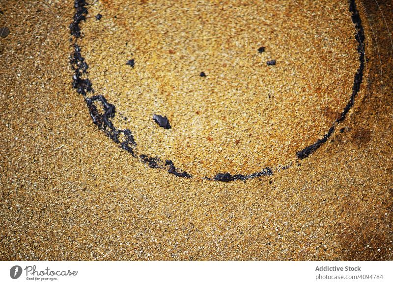 Wet sand texture with circle trace wet surface pollution concept oil round imprint dark drop spot old rusty coast nature coastline shore material beach rough