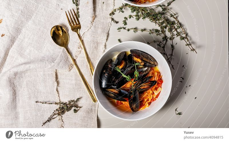 Food banner. A portion of mussels with vegetables in a white bowl on a light background. Delicious and healthy seafood. Shellfish. Top view food banner