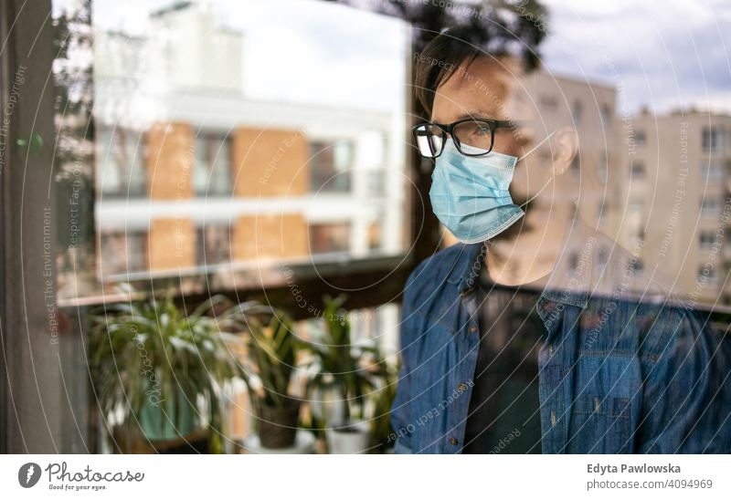 Man with face mask looking out of window home house flat lockdown stay at home man male young adult people one person apartment lifestyle sad lonely covid