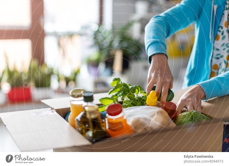 Woman unpacking box of food at home supermarket store fruit vegetables healthy groceries grocery organic fresh kitchen diet meal cooking eating house flat