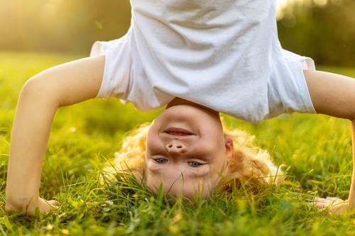 Child doing headstand in park hand stand upside down handstand exercising sport healthy vitality active people child boy little boy kids childhood outdoors