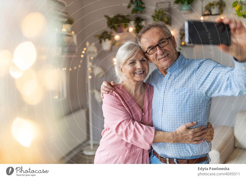Senior couple in the living room taking selfie with smartphone people woman adult senior mature casual attractive female smiling happy Caucasian toothy enjoying