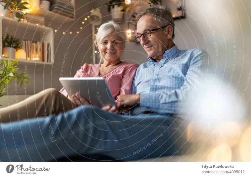 Mature couple using a tablet while relaxing at home people woman adult senior mature casual attractive female smiling happy Caucasian toothy enjoying two people
