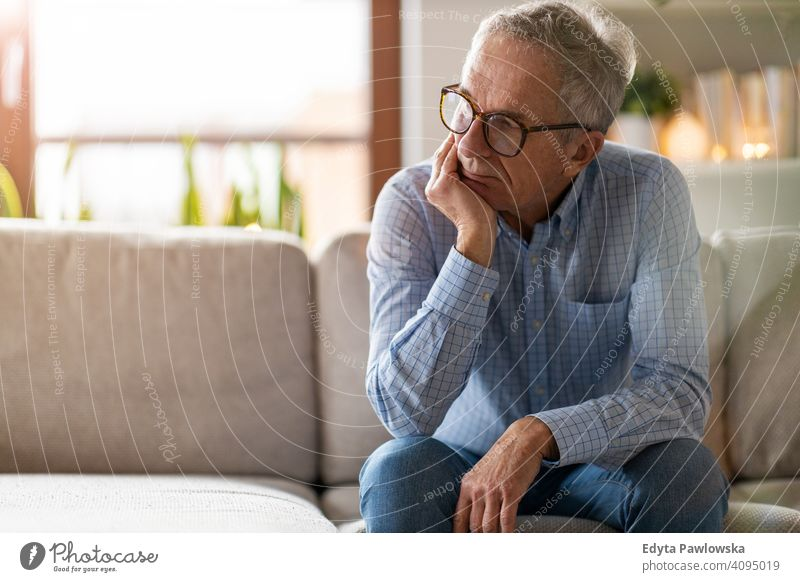 Worried senior man sitting alone in his home people one person mature pensioners retiree retired retirement old elderly gray hair caucasian adult lifestyle male