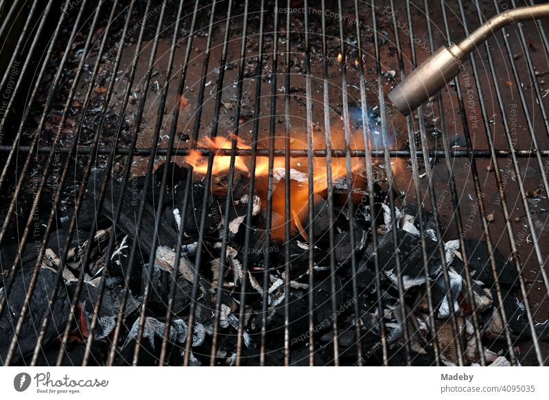 Gas flame of a welding machine for heating the embers of a charcoal barbecue at a barbecue in Rudersau near Rottenbuch in the district of Weilheim-Schongau in Upper Bavaria