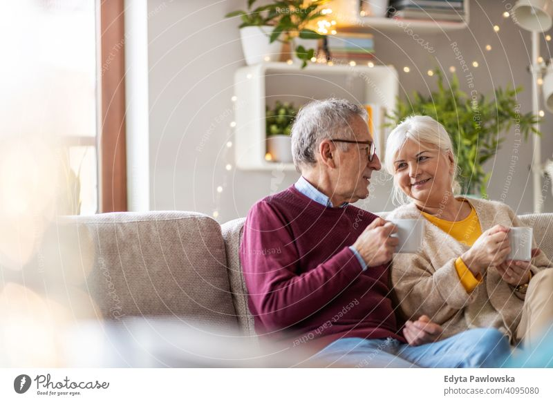 Portrait of a senior couple relaxing at home people woman adult mature casual attractive female smiling happy Caucasian toothy enjoying two people love