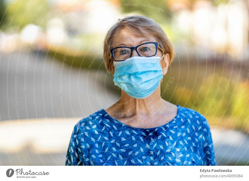 Portrait of senior woman wearing protective face mask outdoors in city people mature casual female Caucasian elderly old grandmother pensioner grandparent