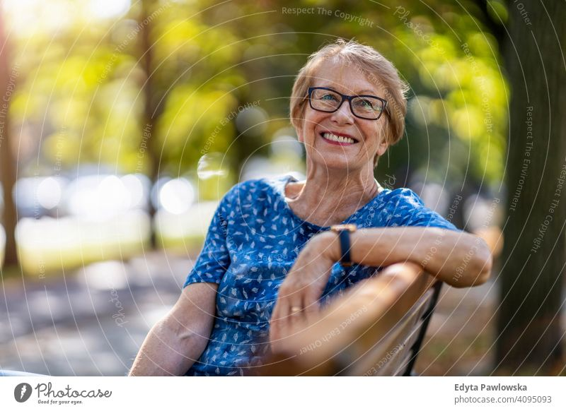 Portrait of a happy senior woman sitting on a bench people mature casual female Caucasian elderly old grandmother pensioner grandparent retired retirement