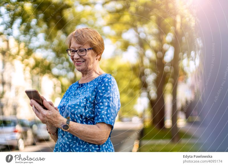 Portrait of a senior woman using mobile phone outdoors people mature casual female Caucasian elderly old grandmother pensioner grandparent retired retirement