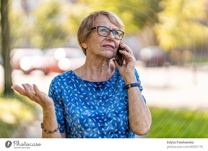 Stressed senior woman using mobile phone outdoors people mature casual female Caucasian elderly old grandmother pensioner grandparent retired retirement