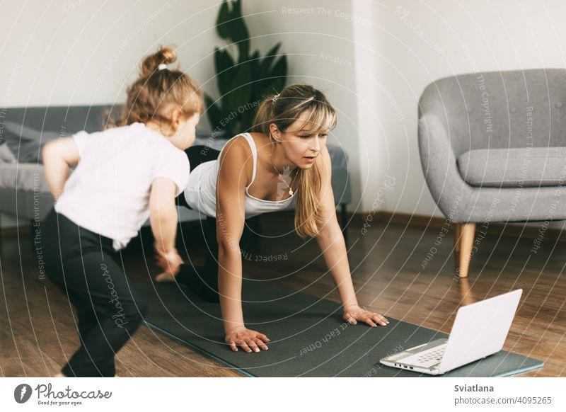 A young mom is doing sports at home and watching a video fitness lesson on a laptop, and her little baby is sitting on a chair. Home training, fitness, sports