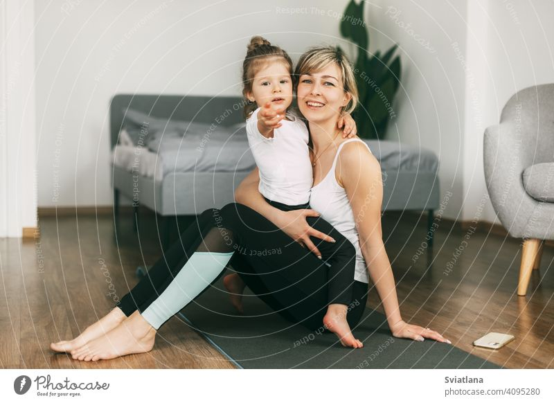 A little girl is sitting on her mother's lap, resting after a fitness exercise, hugging her, smiling, looking at the camera. The concept of a healthy family lifestyle