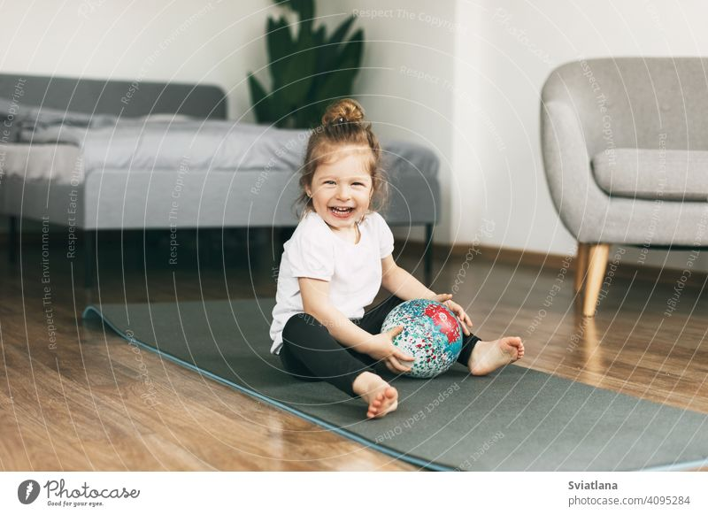 A small child plays on a sports mat with a ball healthy baby girl caucasian fun childhood happy cute kid smiling fitness toddler exercise beautiful little