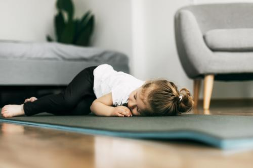 A little girl lies on a yoga mat in the bedroom and rests after a game baby happy lying floor play small child cute resting person human indoors adorable people