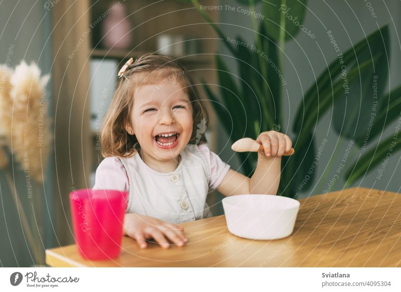 A little girl eats porridge from a white bowl, a girl has breakfast sitting at the table. Healthy breakfast, healthy food child eating plate baby cute childhood