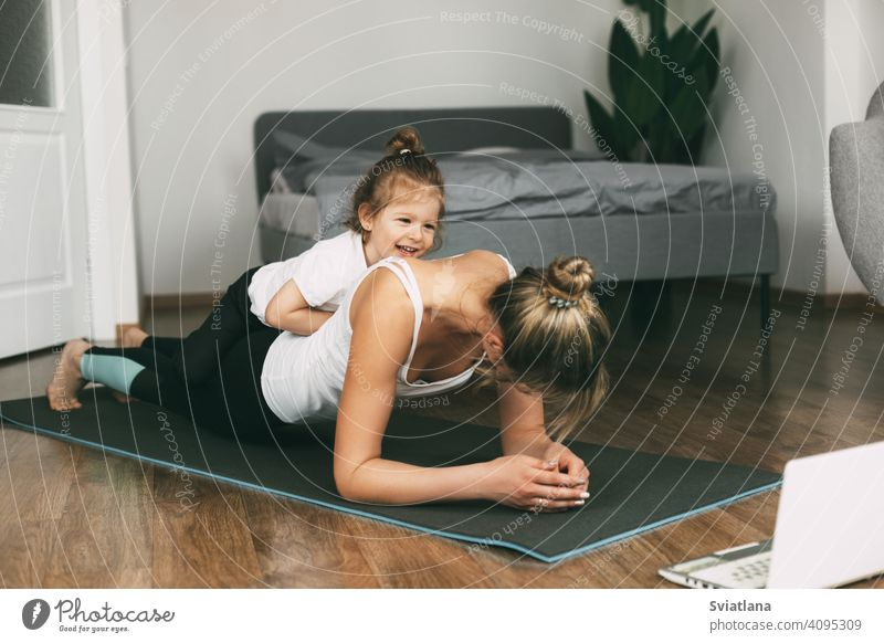 A young sports mom and a girl together do exercises at home. Healthy development of parents and children, healthy lifestyle woman fitness mat beautiful little