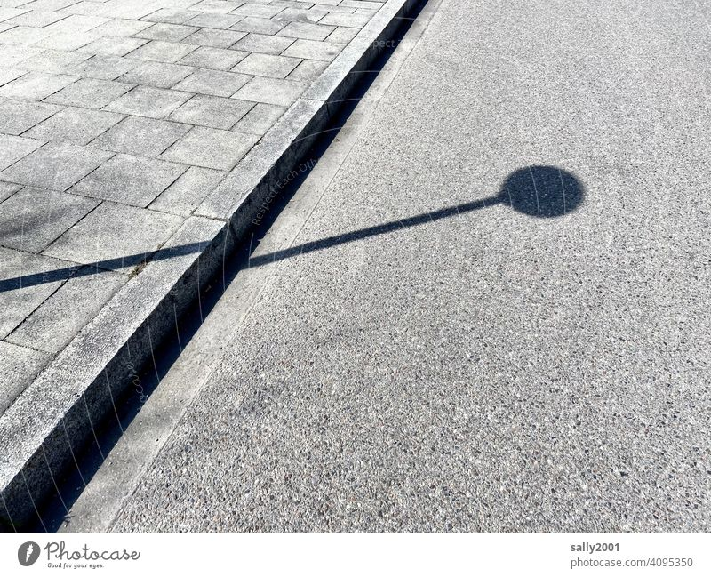 Shadow of a no stopping sign Street Prohibition sign No standing Round Point handle Sidewalk off slabs Curbside Goose shadow cast Gray Lanes & trails