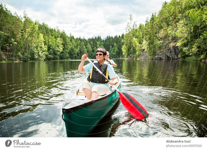 Happy mature couple in life vests canoeing in forest lake. Sunny summer day. Tourists traveling in Finland, having adventure. active activity beautiful discover