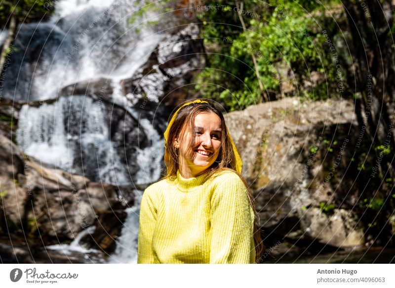Young blonde girl in yellow sweater posing at the Nogaledas waterfall, Extremadura Spain. young looking cascade extremadura spain exploration freedom horizontal