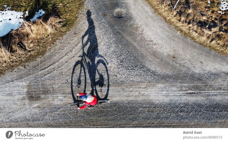 Aerial shot with a drone of a cyclist on a road with shadow Aerial photograph drone photo Spring Sports Cycling Bicycle Woman Driver Driving Street