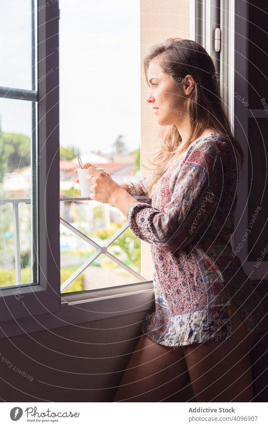 Girl in a shirt with a cup of coffee or tea looking out the window in the morning woman pretty awake joy girl beauty indoors view home rest lifestyle beautiful