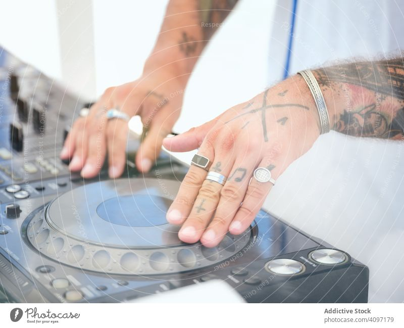 Anonymous DJ tuning music during party dj tune audio board mixer work tattoo club stage rings entertainment sound button turn hand body part hands control