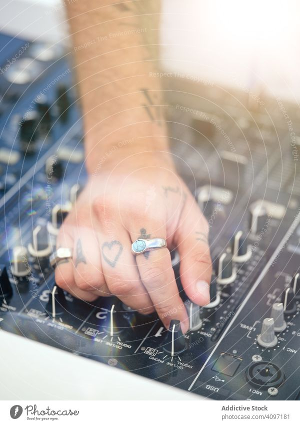 Anonymous DJ tuning music during party dj tune audio board mixer work tattoo club stage entertainment sound button turn hand body part control equipment