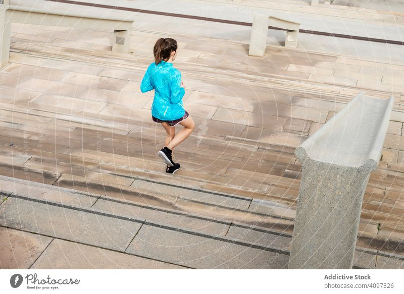 Young runner woman training climbing stairs on the streets of Ba healthy sport active female marathon athlete race lifestyle girl fit outdoor fitness tracker