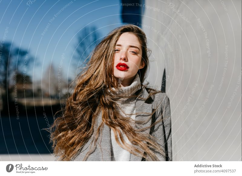 Young woman in coat on windy day stylish street wall city building female urban fashion cool young model outfit warm weather exterior lady long hair trendy