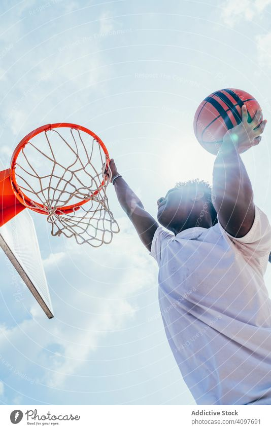 African American sportsman hanging on basketball lap kicking net slam dunk game player stadium playing sportswear activity field male powerful fit athlete