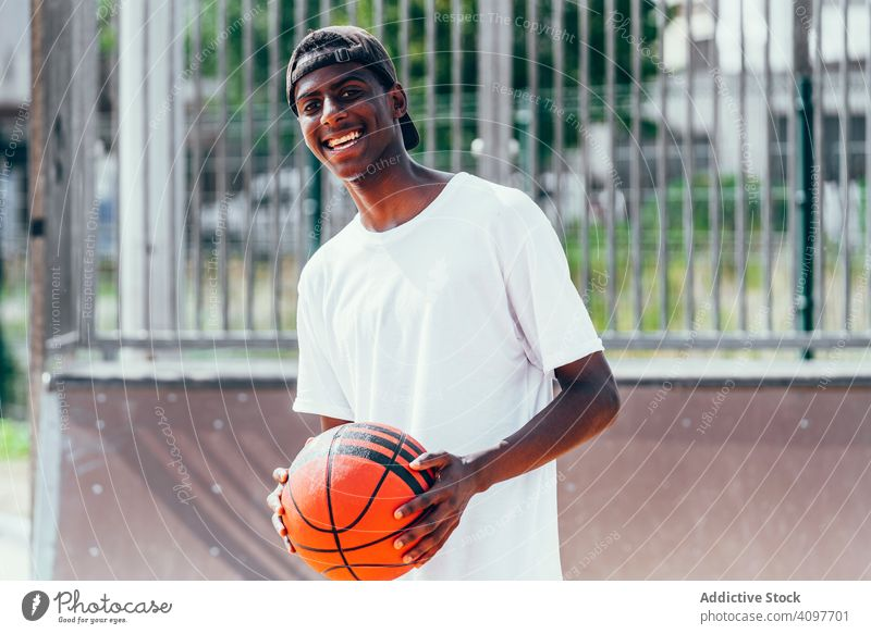Black sportsmen with ball smiling and looking at camera player basketball activity athlete skill action black african american court athletic training