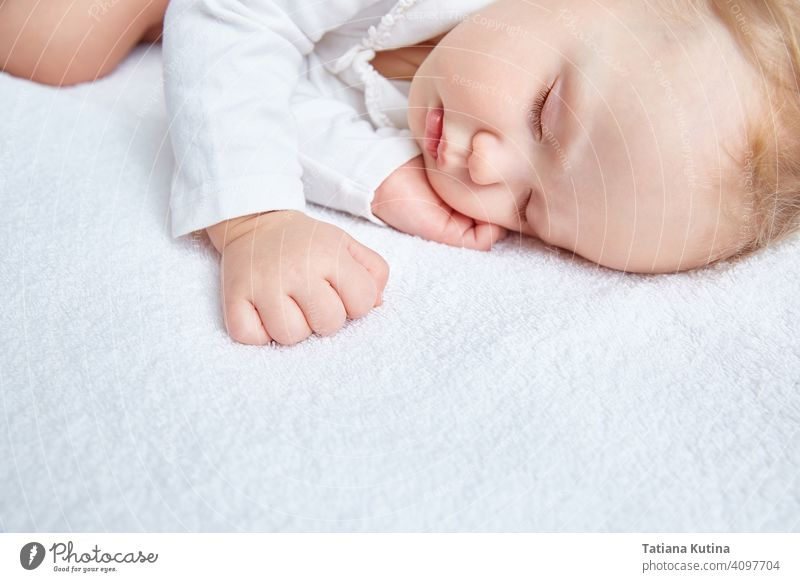 Cute baby sweetly sleeps on white bed linen in white clothes. Close-up. Beautiful healthy soft skin, long eyelashes. child cute little kid portrait small infant