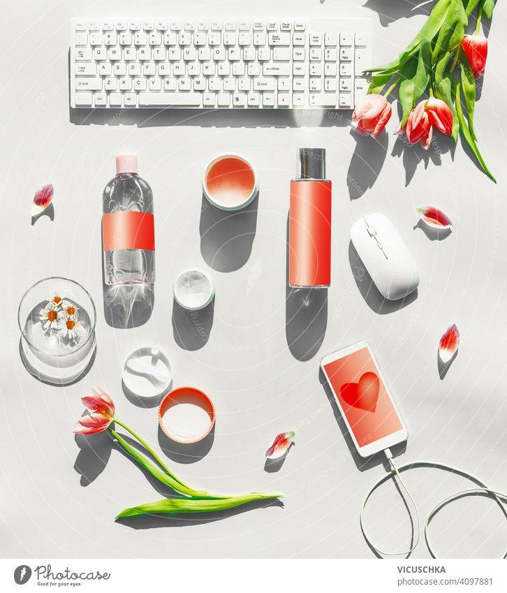 Cosmetic products with mock up on white desktop. PC keyboard , smartphone with blank screen and wire and pink tulips flowers in sunlight. Top view. Flat lay. Springtime. Beauty blog layout.
