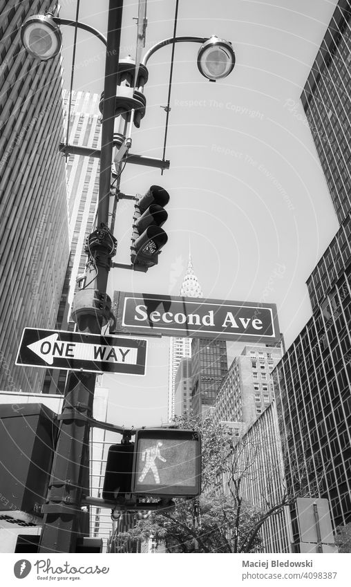 Manhattan cityscape with Second Avenue and One Way street signs on a traffic light post, New York City, USA. black and white one way skyscraper NYC B&W building