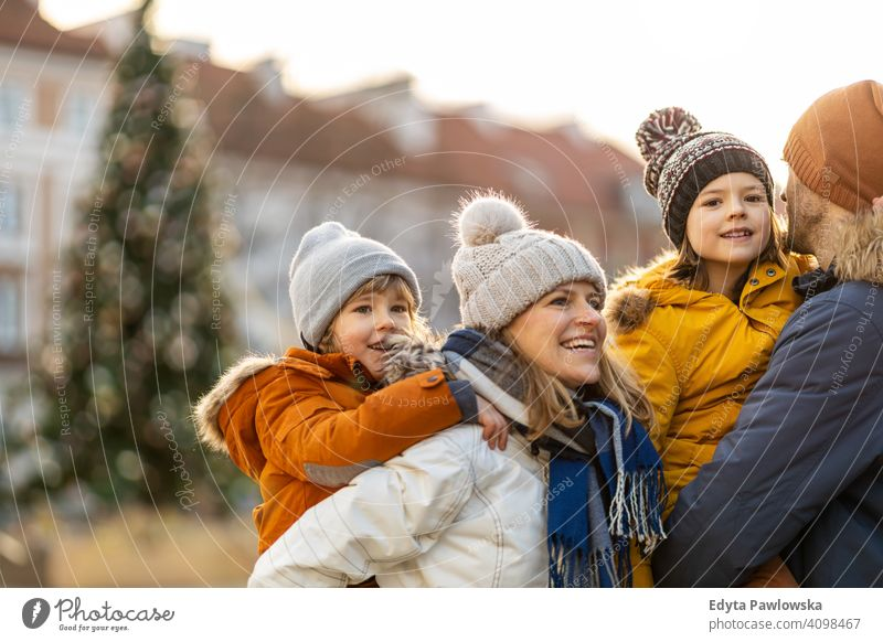 Happy young family having fun outdoors during Christmas winter man autumn father woman mother parents relatives son boys kids children relationship together