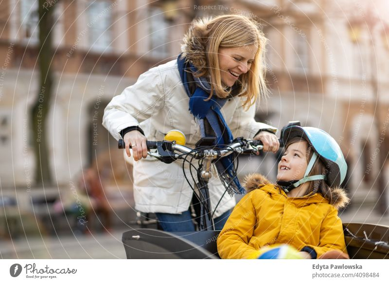 Young woman and her son riding the bicycle in a city young wearing bike helmet cycling winter autumn mother family parents relatives boy kid children