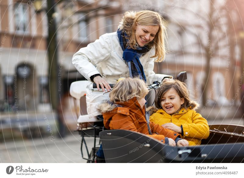 Mother checking on her children who is riding in the front section of a cargo bike cycling transport tricycle healthy active bicycle biking modern