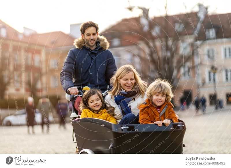 Young family riding in a cargo bike together cycling transport tricycle healthy active bicycle biking modern sustainable transport ecological travel young