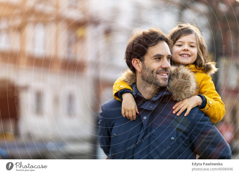Dad and son hugging outdoors young carrying piggyback embracing winter man autumn father family parents relatives boy kids children relationship together