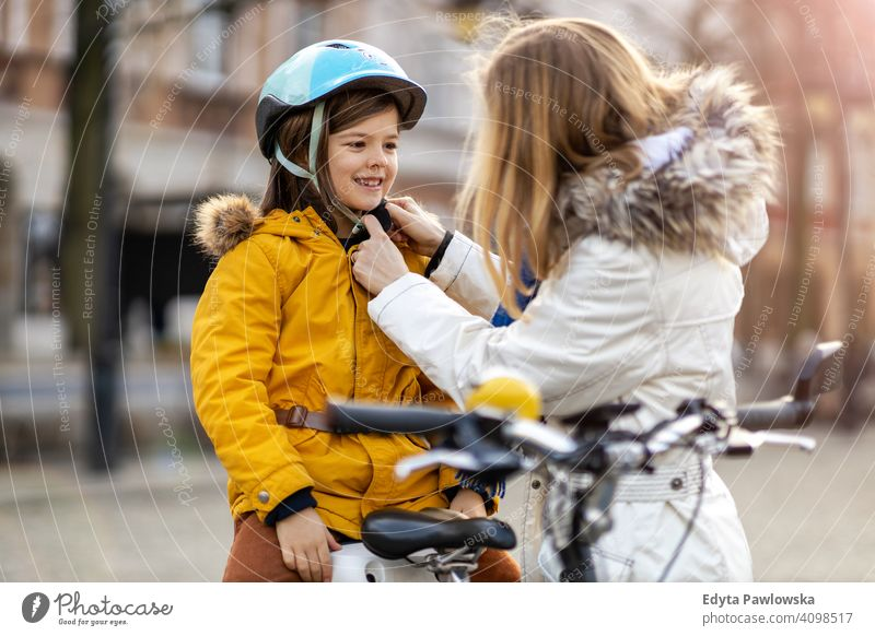 Mother putting bicycle helmet on her son young wearing bike cycling winter woman autumn mother family parents relatives boy kid children relationship together