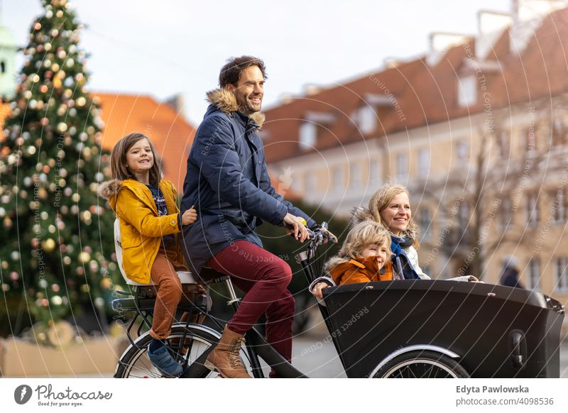 Young family riding in a cargo bicycle during Christmas cargo bike cycling transport tricycle healthy active biking modern sustainable transport ecological
